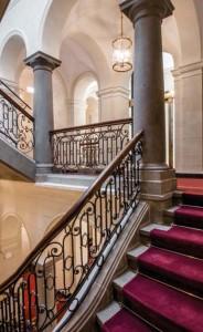 Das imposante Treppenhaus führt zu einem gläsernen Lift