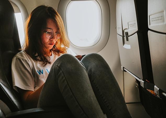 Junge Frau am Fenster im Flugzeug