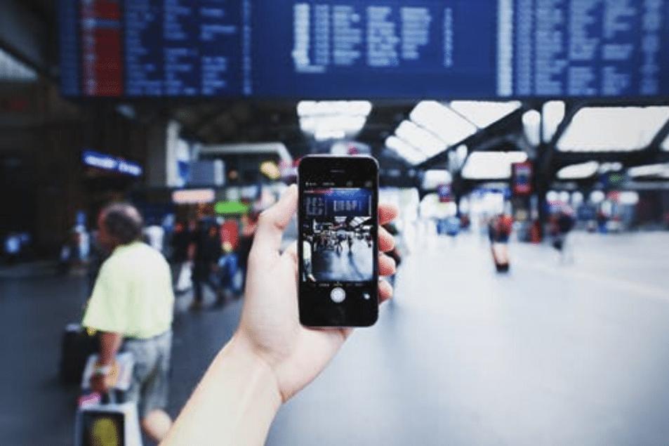Smartphone in der Hand am Flughafen/Bahnhof
