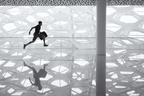 Schwarz/Weiß rennender Mann mit Koffer